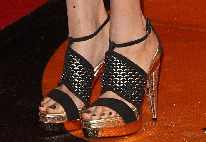 Kesha shows off her feet in gold and black platform sandals