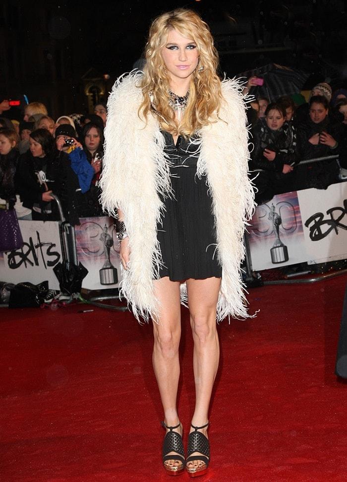 Kesha aka Ke$ha flaunts her legs in a black Dolce & Gabbana cocktail dress and a feathered coat from Temperley London
