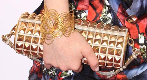 Amanda Seyfried showing off her jewelry and gold clutch handbag