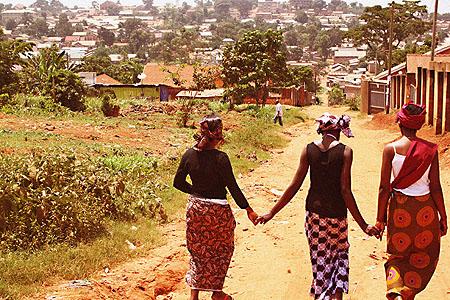Three young Ugandan women walking hand in hand
