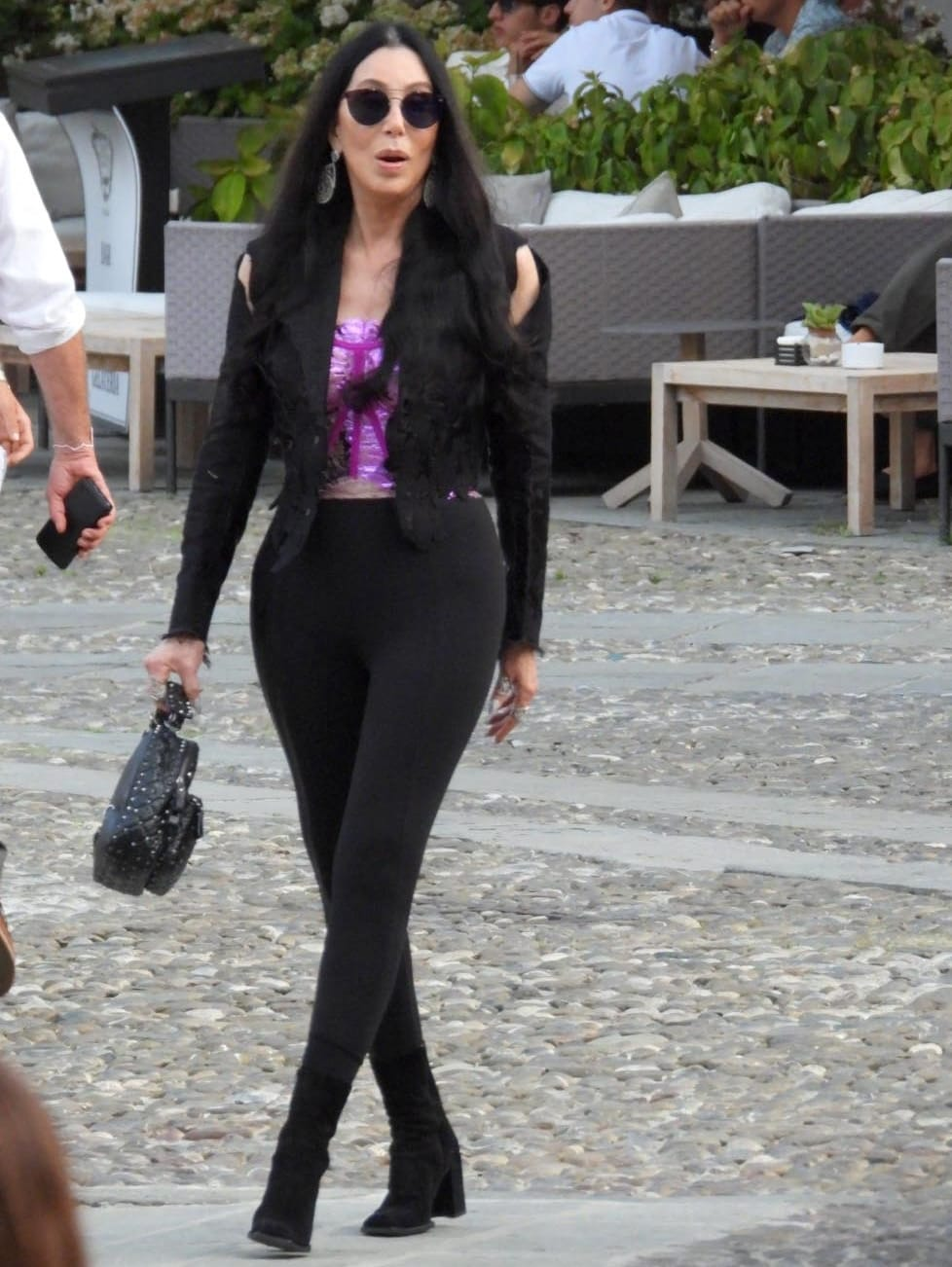 Cher wears black pants and a purple sequined top underneath a black blazer