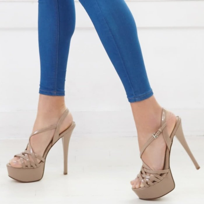 Crisscrossing straps showcase your pretty pedi in nude sandals lifted by a sky-high heel and wrapped platform