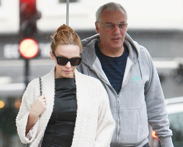 Kylie Minogue rocks an all-neutral outfit out in the rain in London
