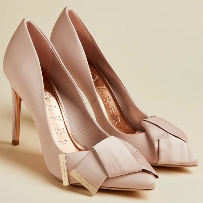 Logo-embellished hardware accentuates the bold bow ornament of this pointed-toe stiletto pump
