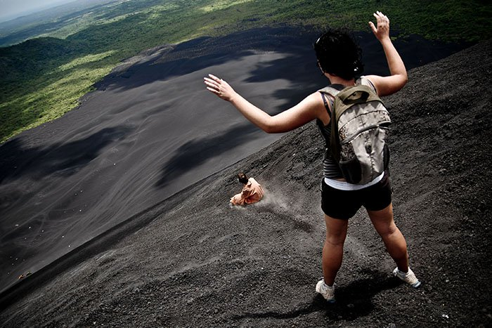 Thrill-seekers volcano-boarding on the slope of the crater of Cerro Negro volcano in Nicaragua