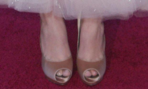 Hailee Steinfeld's feet in nude satin Ferragamo pumps