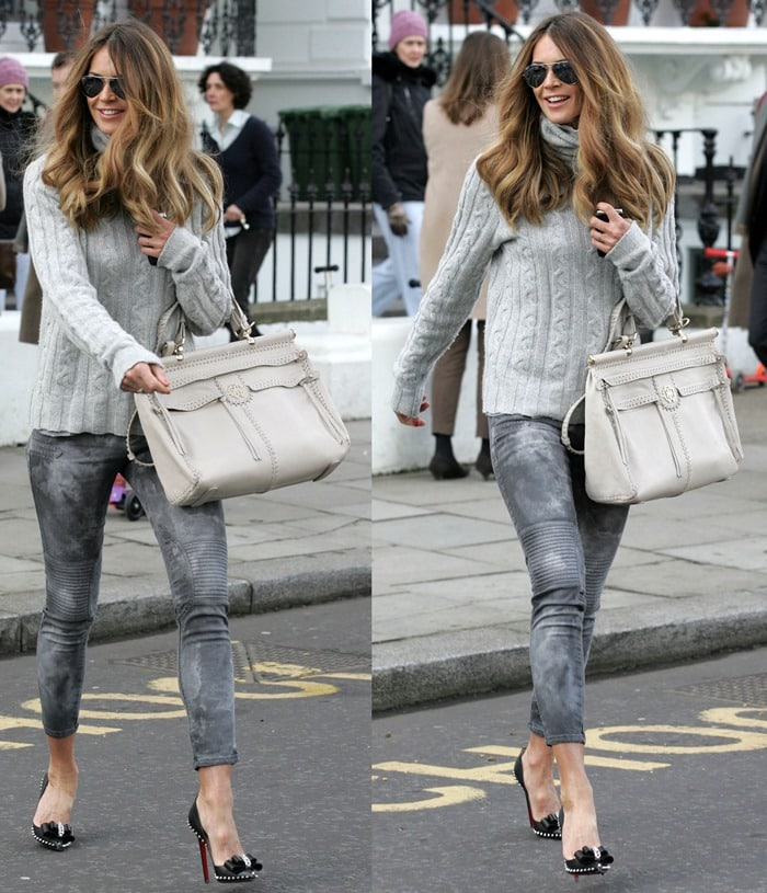 Elle MacPherson wearing a cable knit sweater, cropped grey moto jeans, and spiked pumps