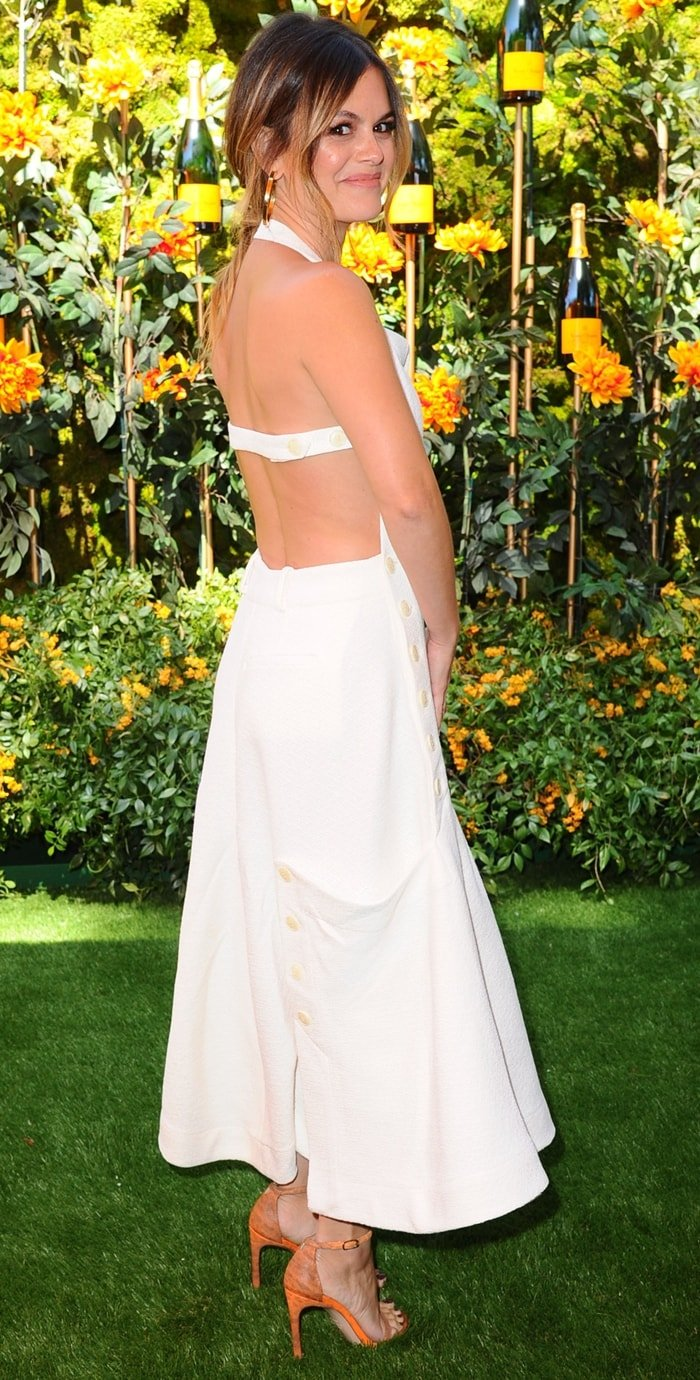 Rachel Bilson in Nudist sandals and a white dress featuring a halterneck, an open back, adjustable straps, a side button fastening, side pockets, and a flared style