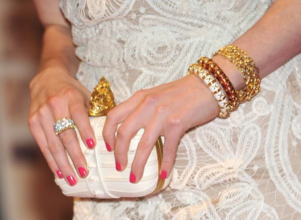 Anne Hathaway carrying a white jaw skull clutch from Alexander McQueen