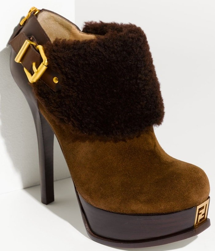 A stacked heel and platform lift a chic suede bootie accented with a cuff of tactile shearling. A signature goldtone logo gleams at the front.