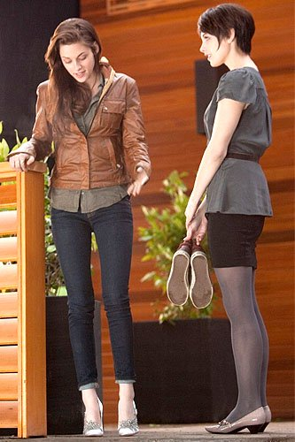 Bella Swan (Kristen Stewart) trying on her high-heeled wedding shoes with soon-to-be sister-in-law Alice Cullen (Ashley Greene)