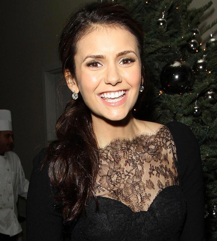 Nina Dobrev wearing a black lace dress