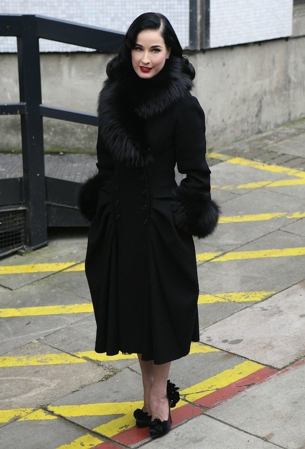 Dita Von Teese wears a fur-trimmed winter coat while out in London
