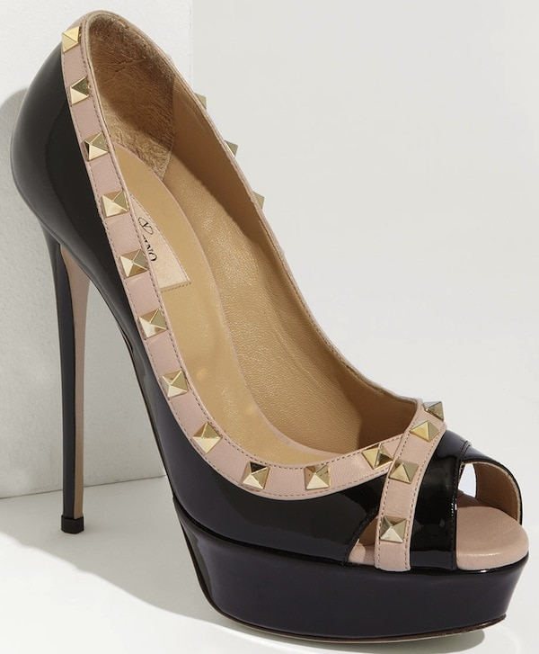 Golden pyramid studs edge a glossy patent pump balanced atop a slim wrapped heel