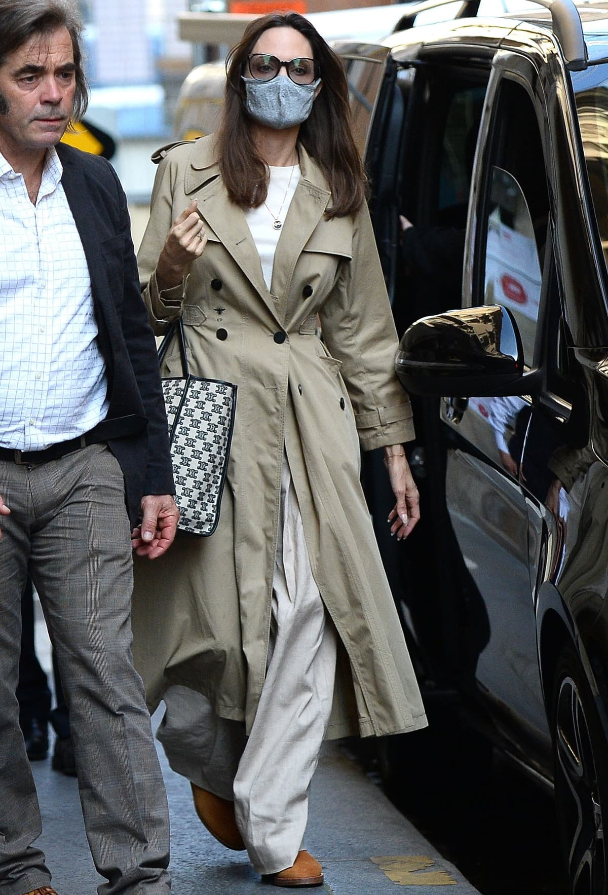 Angelina Jolie wears a Dior trench coat and totes a Celine Horizontal Cabas bag in textile with Triomphe embroidery outside her hotel in Paris