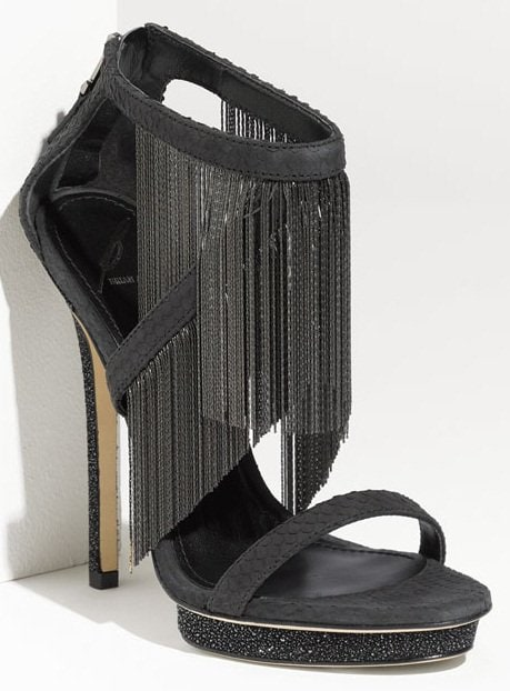 Captivating chain fringe drapes dynamic allure over a strappy, snake-stamped sandal supported by a sparkling platform and heel