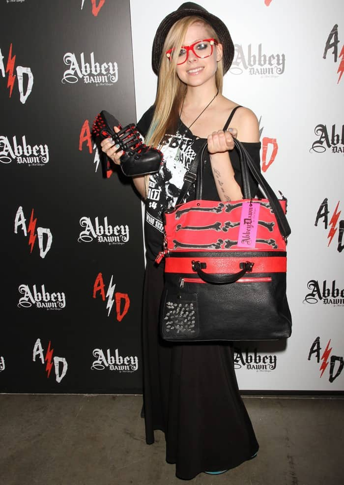 Avril Lavigne holding a pair of Abbey Dawn shoes