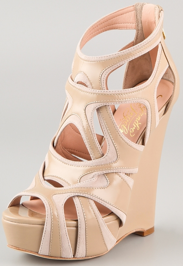 These wedge sandals feature patent leather details at the crisscross suede straps and exposed zip at the heel cap