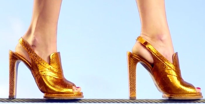 Model wearing high heels while making her way across a tightrope