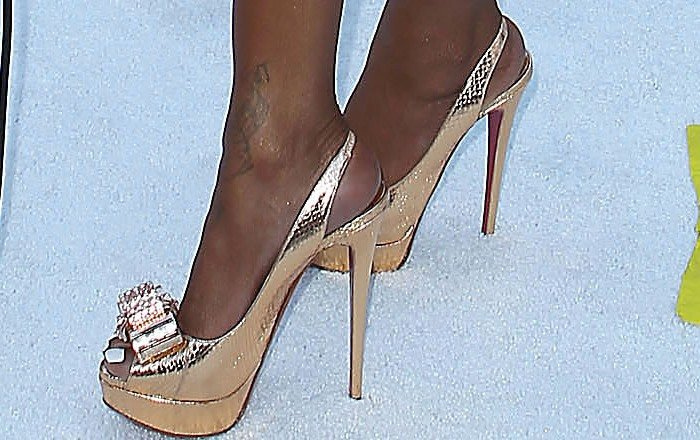 Brandy turns her foot tattoo toward the camera as she flaunts it in a pair of metallic Christian Louboutin platforms