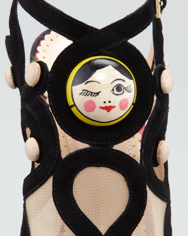 This shoe features a cool light wooden heel and platform with black suede straps and ultra cool Matryoshka doll face details