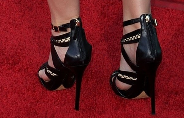Elegant lacings twine corset-chic across twisted leather sandals worn by Emma Watson