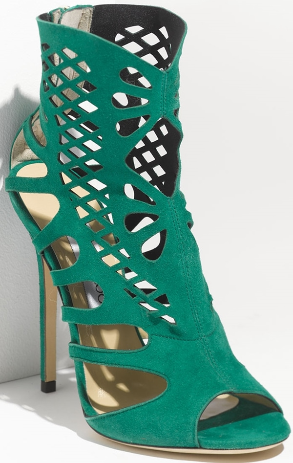 Elegant cutouts cage the foot in delicate geometry, realized in emerald green suede