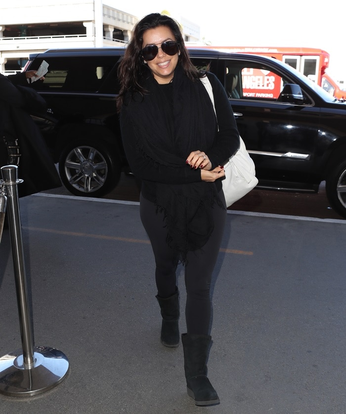 Eva Longoria flashed a cheerful smile as she maked her way into LAX Airport in Los Angeles on December 1, 2017