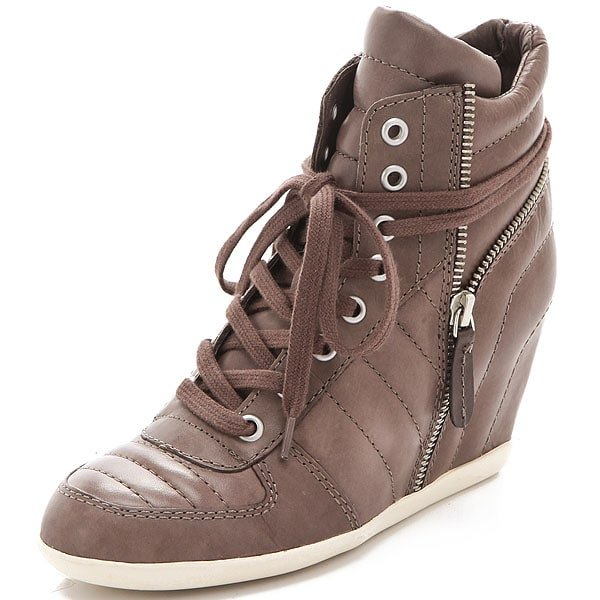 Snug leather wedge sneakers cut a tough, street-chic line, an aesthetic reinforced by puffed panels and a separated, wraparound heel zip