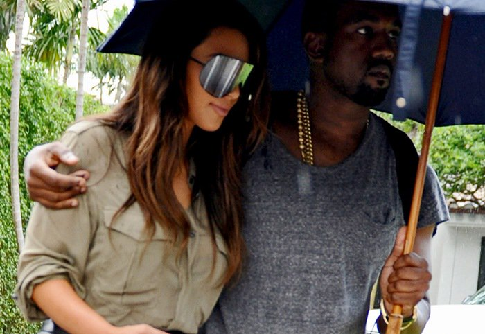 Kim Kardashian and Kanye West cuddled together under an umbrella