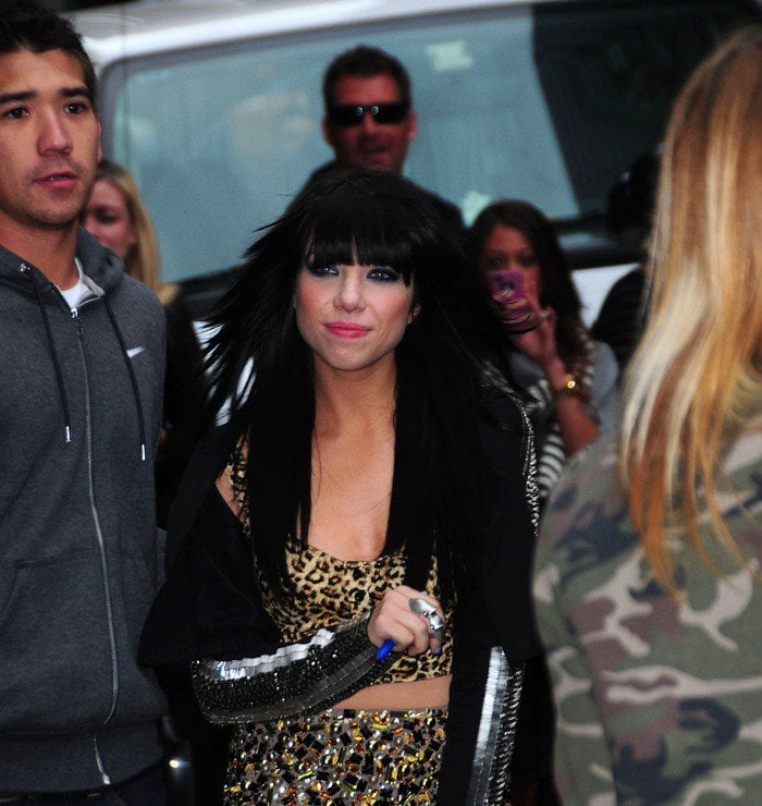 Carly Rae Jepsen wears a studded jacket overtop of a leopard print bra top and matching sequined skirt