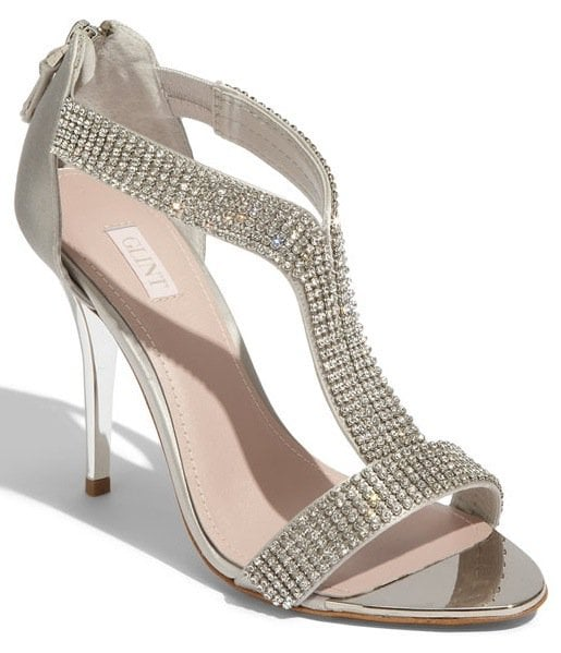 Allover rhinestone studs add a bit of tough-girl glamour to a shimmering sandal on a daring stiletto heel