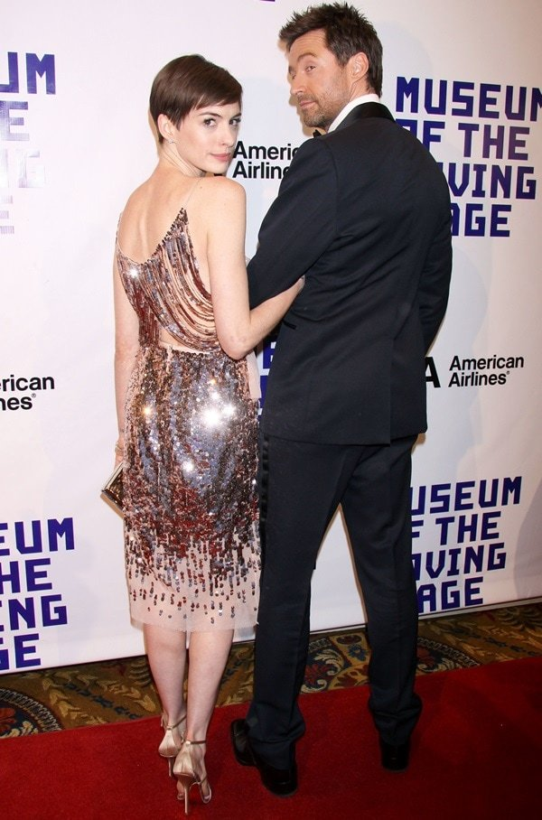 Anne Hathaway wears a sequined pink Stella McCartney dress while posing with Hugh Jackman