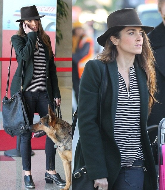 Nikki Reed wearing a striped shirt, cropped skinnies, and a black jacket at LAX along with her two German Shepherds on December 10, 2012