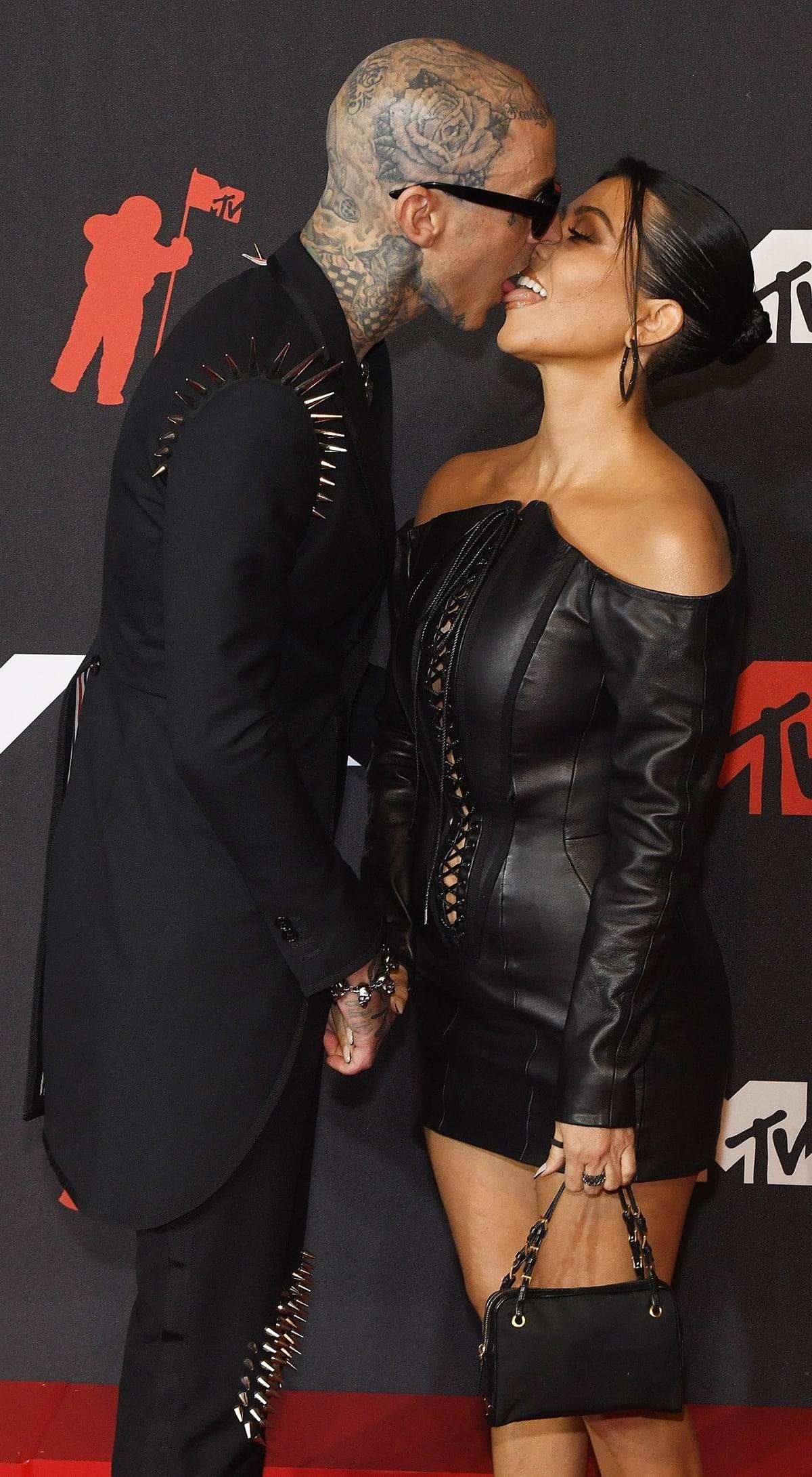 Wearing a black leather dress with long sleeves, Kourtney Kardashian kisses her boyfriend Travis Barker