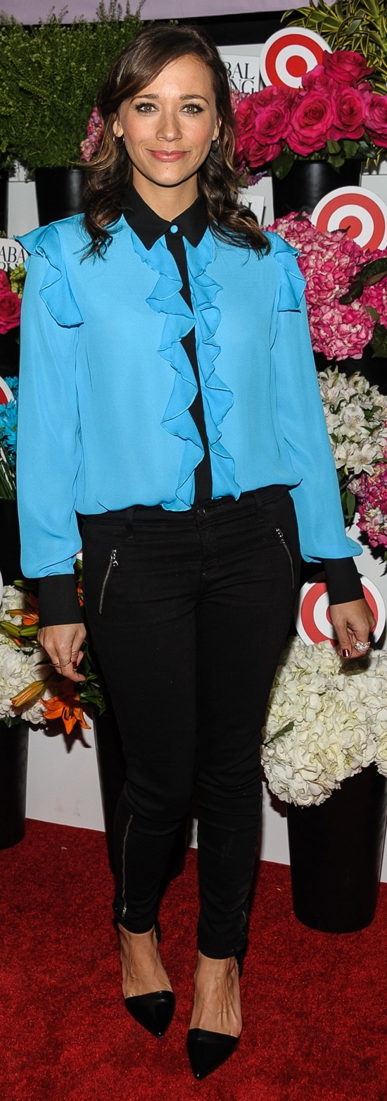 Rashida Jones in black zipper-detailed pants and a bright blue button-up