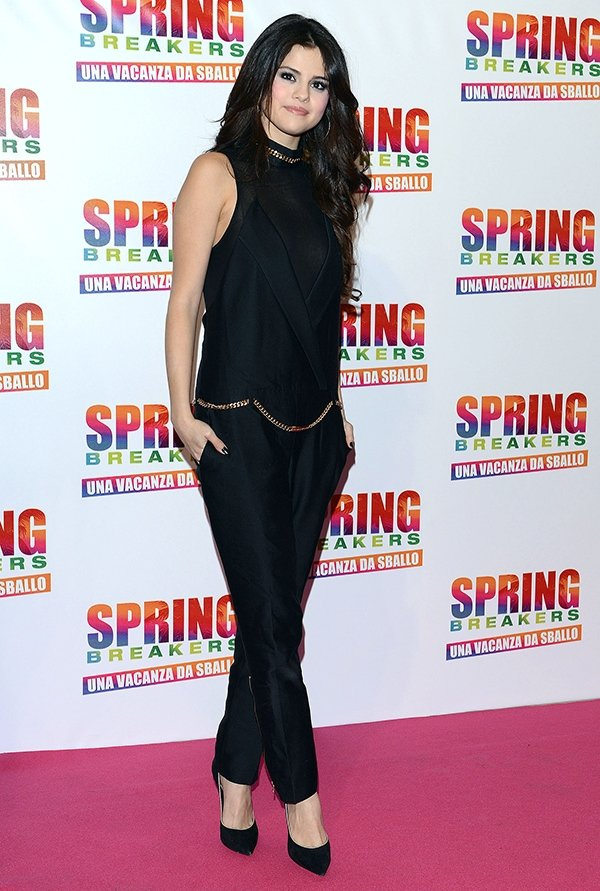 Selena Gomez wears her hair down in an all-black Thomas Wilde jumpsuit on the pink carpet