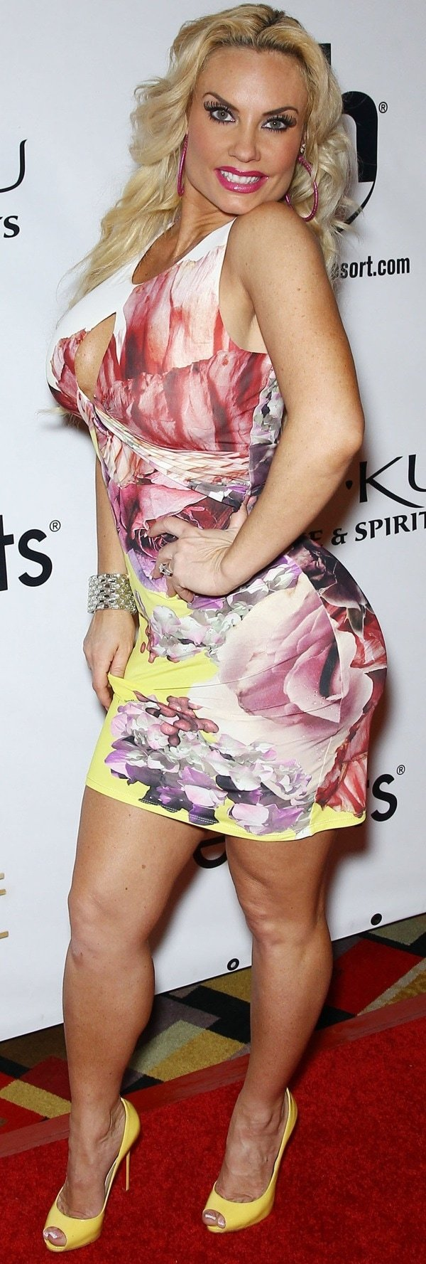 Coco Austin wearing a floral-printed dress in pink, white, and yellow