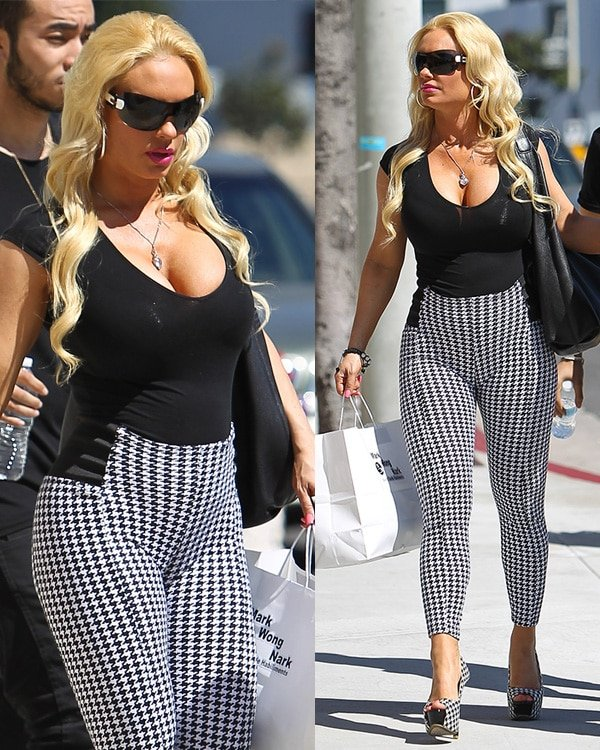 Coco Austin wears a black plunging neckline shirt and tight-fitting houndstooth trousers