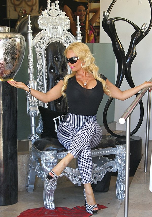 Coco Austin sitting on a throne chair while wearing houndstooth shoes