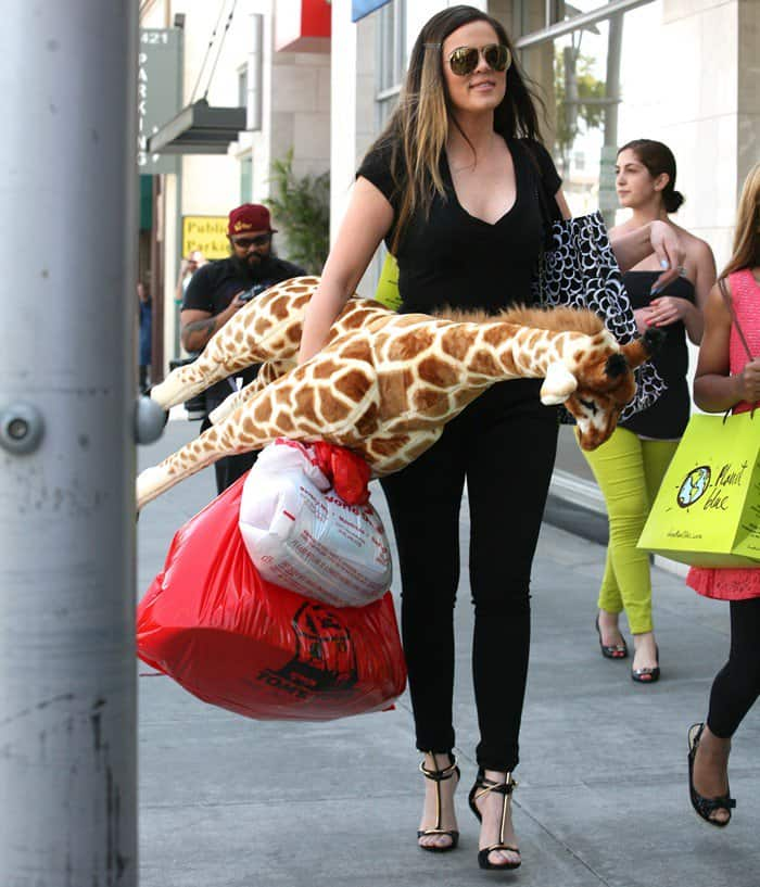 Khloe Kardashian was seen carrying a bunch of toys and wearing an all-black ensemble consisting of tight black trousers and a tight v-neck t-shirt