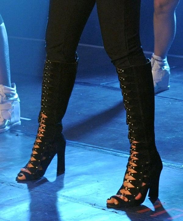 Nicole Scherzinger inblack knee-high boots with cutout details