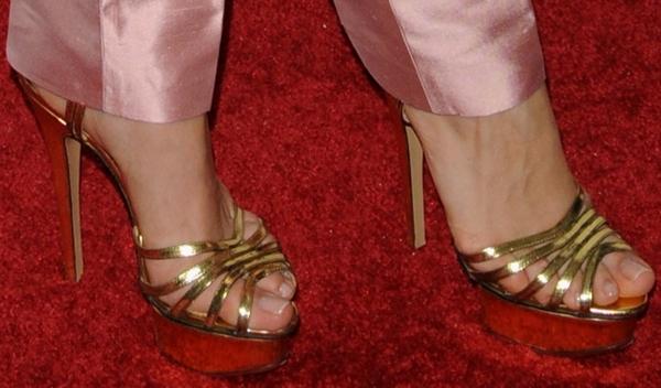 Olesya Rulin's feet in strappy gold platform sandals