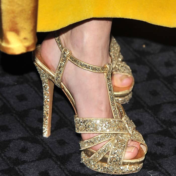 Anna Friel mixing glittery gold sandals with a yellow gold dress