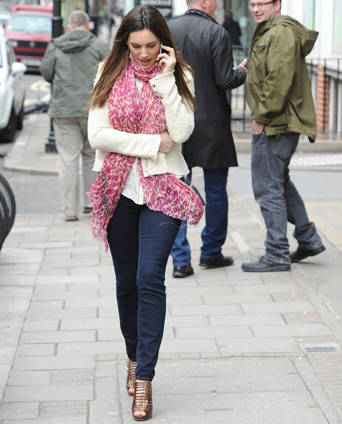 Kelly Brook wearing skinny jeans, a white knit blouse, a black Chanel crossbody bag, a pink printed scarf, a scarf, and brown leather buckled 'Manon' booties from Christian Louboutin