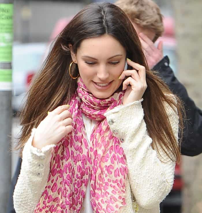 Kelly Brook wears a pink printed scarf with a white knit blouse