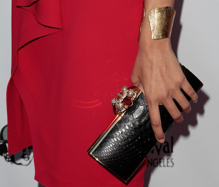 Freida carried a black royal ornament crystal satin clutch by Thalé Blanc and accessorized with a Joan Hornig brass lizard cuff