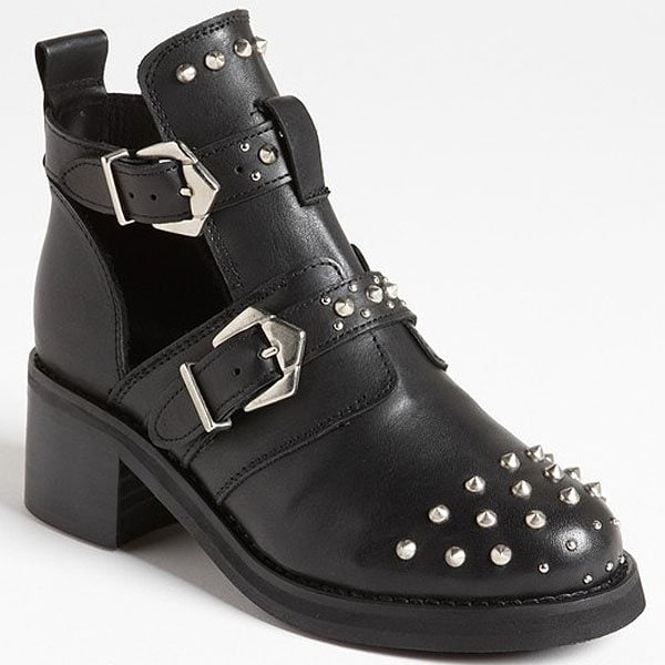 Silvery studs splash a chunky leather boot crafted with side cutouts that flash a little skin
