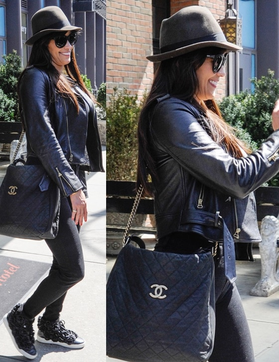Paula Patton wearing a black leather jacket over an all-black outfit, a quilted Chanel purse, plus a black hat