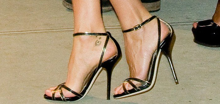 Gisele Bundchen's feet instrappy snakeskin sandals featuring gold trimming and buckle closures